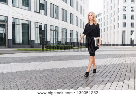 Beautiful business woman in black suit with laptop confidently striding across square