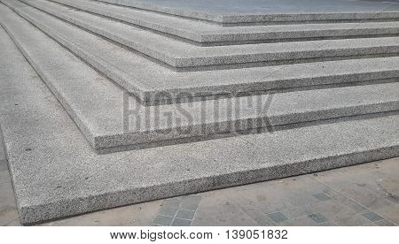 view looking up stack of six wide, gray concrete steps with granite finish, with steps on both sides a corner, points of the corners angled toward camera, descending to the left of the photo