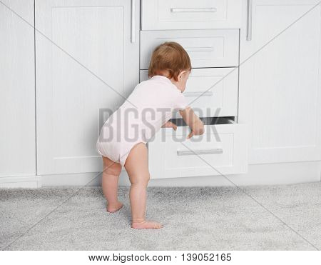 Little child playing with drawer poster
