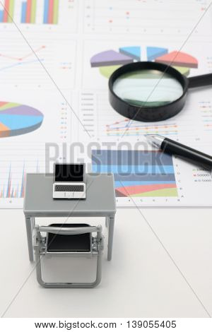 Notebook PC and business documents with numbers and charts. Concept of workplace of the businessman.