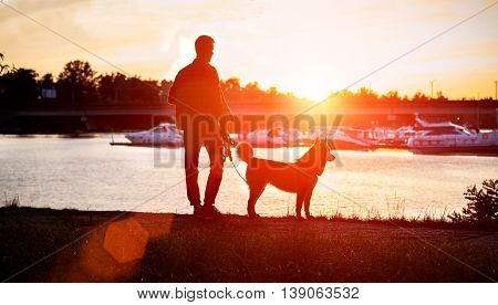 the guy with the dog watching the sunset on the dock.