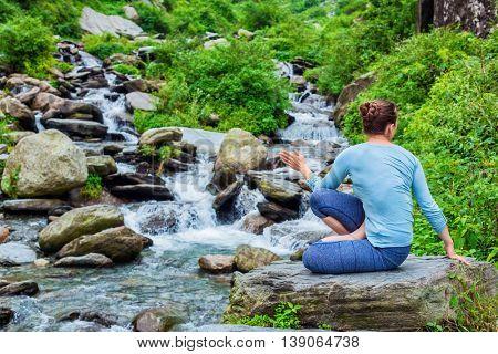 Yoga exercise outdoors -  woman doing Ashtanga Vinyasa Yoga asana Marichyasana D seated spinal twist pose at waterfall in mountains