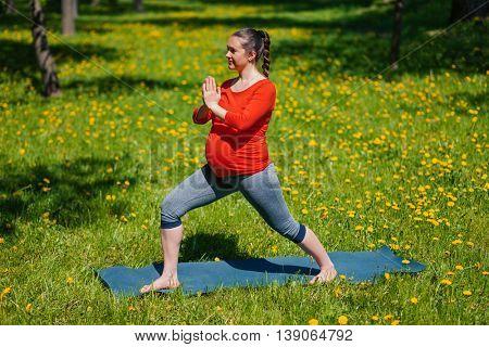 Pregnancy yoga exercise - pregnant woman doing yoga asana Virabhadrasana warrior pose outdoors on grass in summer