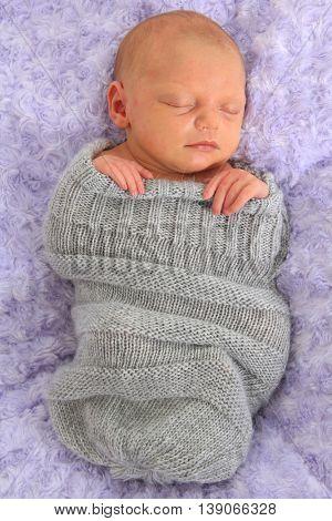 Newborn baby girl asleep on a purple blanket.