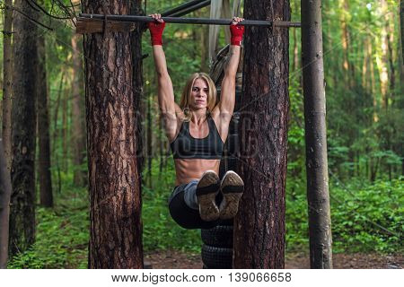 Fit woman doing hanging leg lifts abs muscles exercise on horisontal bar working out outside.