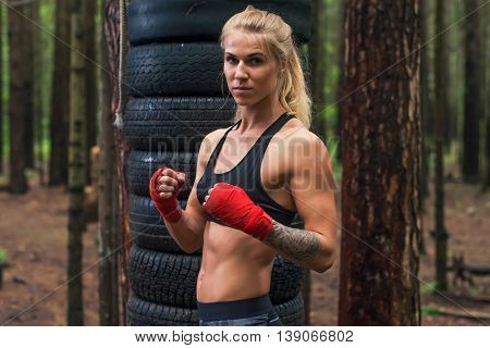 Woman boxer professional fighter posing in boxing stance, working out outdoors.