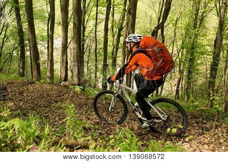 Biker with orange backpack on the forest road