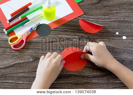 The Child Makes A Postcard With Ladybird. Child Glues Paper Items. Glue, Paper, Scissors On A Wooden