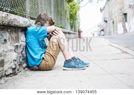 A Photo of Sad and Stressed Kid sit by the Wall outdoor