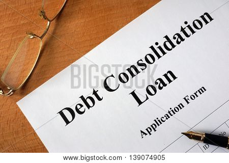Debt consolidation loan form on a wooden table.