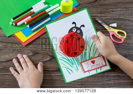 Colorful Paper Card With Ladybug, Grass, And The Words I Love Summer. Scissors, Paper, Crayons And G