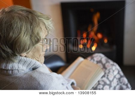 Senior Woman Reading Book By Fire At Home