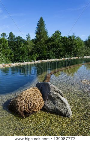 Textile fabric net in natural swimming pond for purifying plants poster