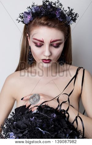 Beautiful cheeky girl in the image of a vampire with bright dark makeup, black vampire bride with a bouquet and a black wreath