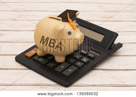 Cost of getting a MBA A golden piggy bank with grad cap and calculator on a wood background with text MBA poster