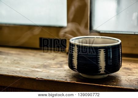 Hot Japan Tea Cup On Wood Bar Beside Window