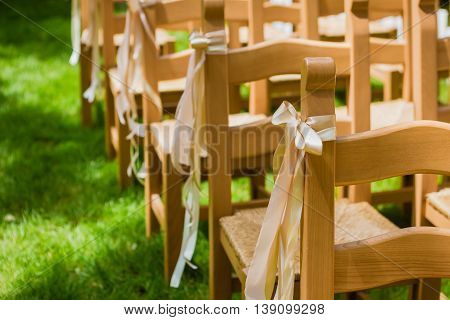 wooden decorated empty chairs on a lawn before wedding ceremony