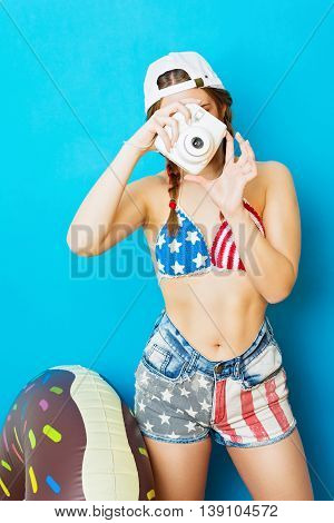 Young woman in American flag bikini and shorts taking a photo using instant camera. Teenage girl photographer against blue background. Retouched, vibrant colors.