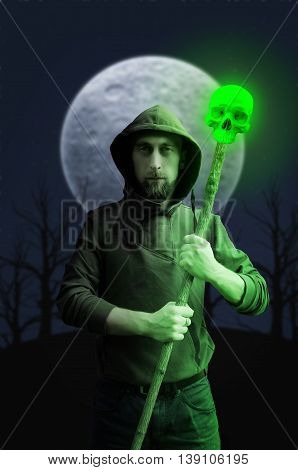 Warlock with luminous skull on fool moon background. Halloween concept. Gothic concept.