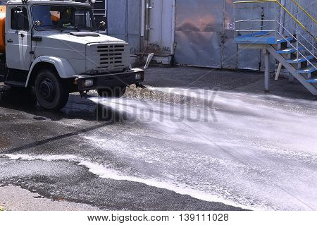 Water truck watering the asphalt at a manufacturing plant for dust suppression.
