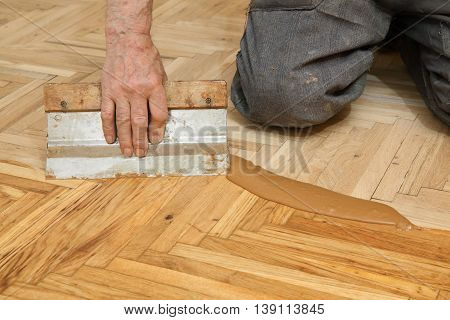 Varnishing of oak parquet floor senior workers hand and tool 77 year old senior worker