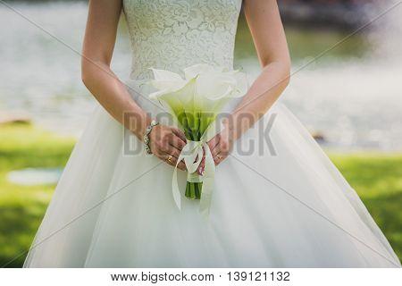 wedding bouquet of flowers calla in bride's hands