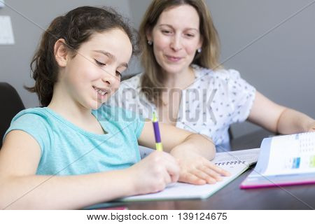 A Mature mother helping her child with homework at home.