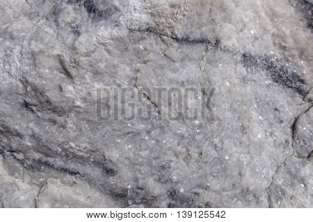 Texture raw rough surface of white marble. Background raw white marble stone in its natural form. Semi-precious stone material for making buildings and interior. Industrial raw materials marble.