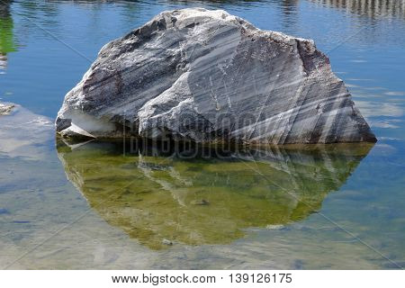 Large monolithic marble stone lays in the clean lake water of career. Raw white gray marble stone. Semi-precious stone material for making buildings and interior. Industrial raw materials marble.