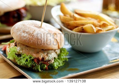 Delicious Burger with Chicken Lettuce Grilled Tomato and Cheese Sauce and Bowl with French Fries closeup Outdoors. Focus on Foreground