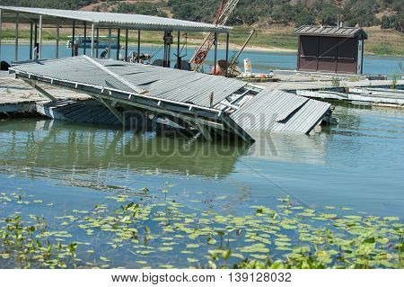 Lake docks broken and collapsing in the water.