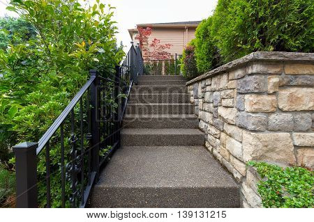 Outdoor stairs with wrought iron black railings stone facade planters and cement steps to house front door entrance