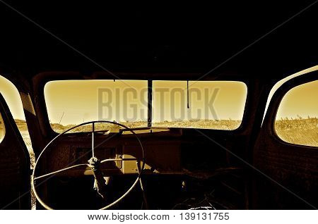 (sepia) The interior of a  neglected and very old pickup truck with a vertical wiper on a roll-out front windshield