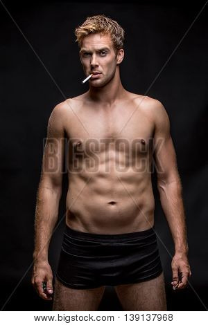 Guy with muscular body in black underpants stands on the black background in the studio. He has a cigarette and a lighter in the hands and a cigarette in the mouth. Vertical low-key photo.