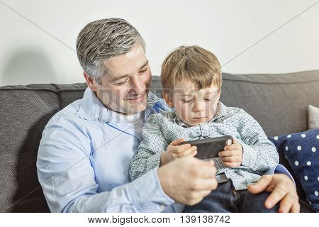 A father and son playing games on mobile phone at home