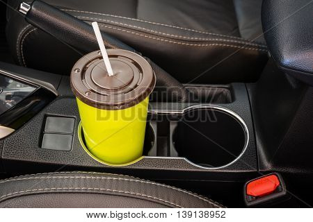 Coffee or tea mugs green placed on the vehicle console in modern luxury car interior