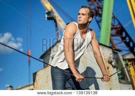 Young man in a white singlet and blue jeans holds the steel rope on the background of industrial zone and blue sky. He looks to the right. Outdoors. Horizontal.