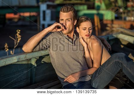Cute couple in the old boat outdoors in the industrial zone. Guy in a gray T-shirt and blue jeans smokes a cigarette and looks into the camera. Nude girl with closed eyes cuddled up to him. Horizontal.