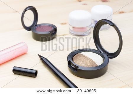 Woman cosmetics include eyes liner and lip gloss and eyeshadow on wood table