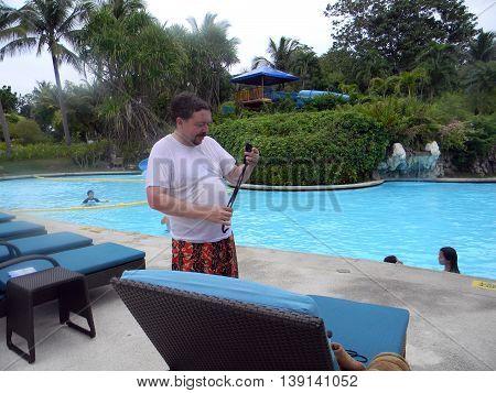 LAPU LAPU, CEBU / PHILIPPINES - JULY 28, 2011: A man adjusts his swimming goggles next to the swimming pool of Shangri-La's Mactan Resort and Spa.