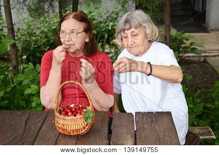 Senior citizens enjoying their day eating cherries