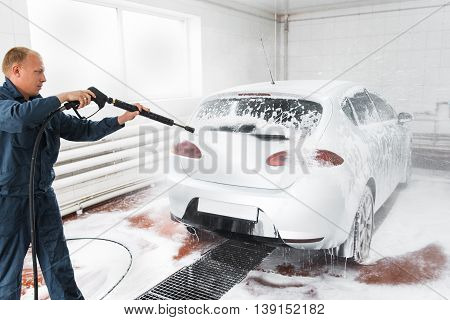Handle carwash concept, man with hose wash white car at service station. Garage worker washing automobile with nosepiece