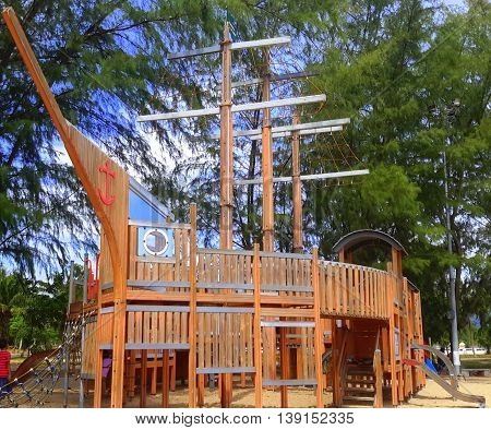 Thai ship-shaped wooden jungle gym with climbing nets, slides, boat masts, boat prow pointing to just left of camera, under pine trees on beach sand, Songkhla, Thailand,
