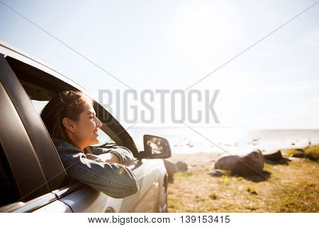 summer vacation, holidays, travel, road trip and people concept - happy smiling teenage girl or young woman in car at seaside