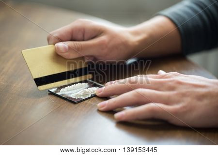 drug use, people, addiction and substance abuse concept - close up of addict hands with crack cocaine drug dose track on mirror and credit card poster