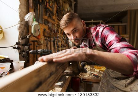 profession, carpentry, woodwork and people concept - carpenter testing wood plank evenness at workshop poster