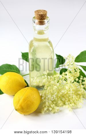 Sambucus nigra elderberry sirup on white background whit shadow. Bottle of excellent syrup with flowers leaves and lemon.