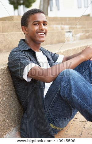 Smiling Male Teenage Student Sitting Outside On College Steps