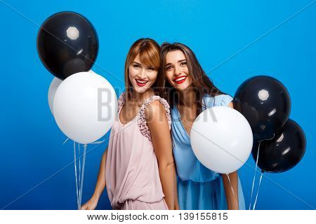 Portrait of two young beautiful girls in dresses looking at camera, holding baloons, laughing, smiling, resting at party over blue background.