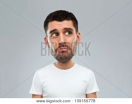 emotion, facial expressions and people concept - sad young man in white t-shirt over gray background looking up (funny cartoon style character with big head)